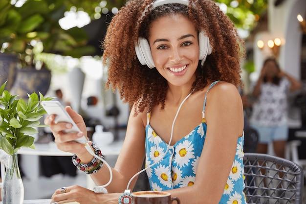 Foto de uma linda mulher mestiça de pele escura com penteado afro ouve a faixa favorita em fones de ouvido, conectada a um smartphone moderno