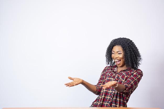 Foto de uma linda mulher negra apontando para o espaço com empolgação
