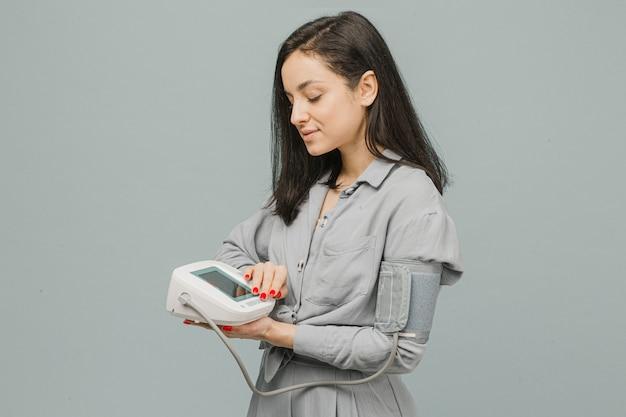 Foto de uma linda mulher segurando um medidor de pressão, verificando a saúde do coração