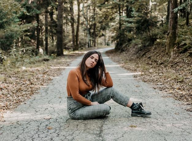 Foto de uma linda mulher sentada em um parque de outono