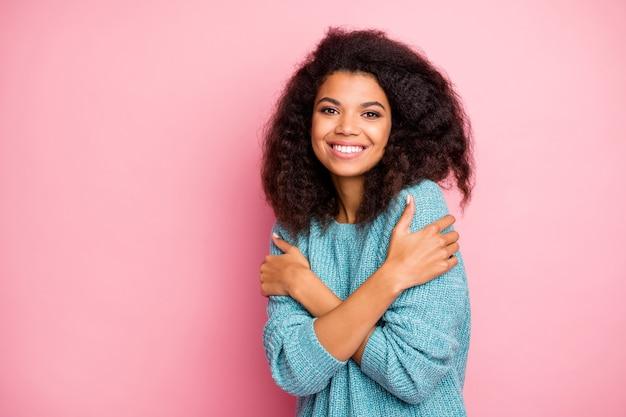 Foto de uma linda namorada bonita e charmosa se abraçando e sorrindo com os dentes no macacão azul, olhando para você com parede de cor pastel isolada de prazer