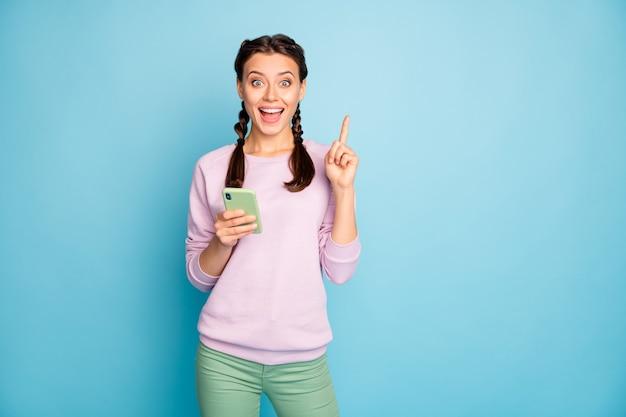 Foto de uma linda senhora engraçadas tranças segurando telefone tem uma nova postagem no blog, uma ideia de texto de anúncio, aumentar o dedo indicador usar um suéter rosa casual calça verde isolada cor azul