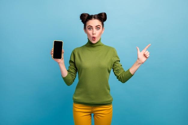 Foto de uma linda senhora gerente de vendas segurar novo modelo telefone inteligente lado do dedo direto espaço vazio boca aberta usar calça verde de gola alta amarela isolada parede de cor azul