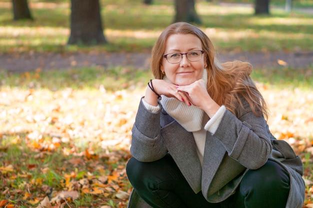 Foto de uma linda senhora loira, folhas amareladas caindo, uma caminhada e um lindo perfume inesquecível de outono, parque da cidade, na rua