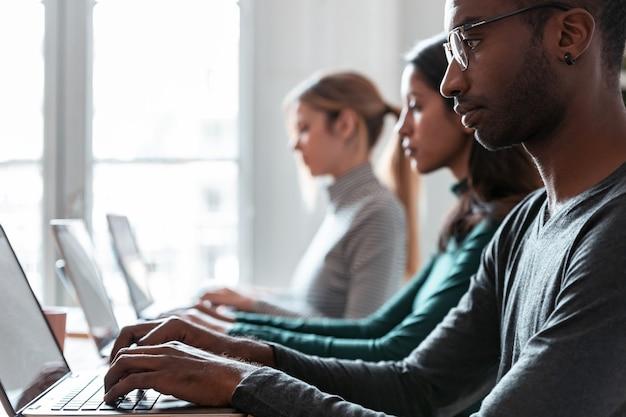 Foto de uma linha de funcionários concentrados trabalhando com laptops em um local de coworking.