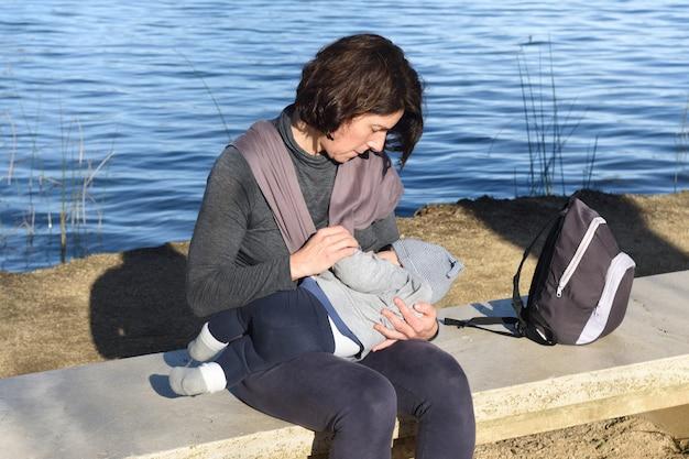 Foto de uma mãe vestida com roupas esportivas amamentando seu filho