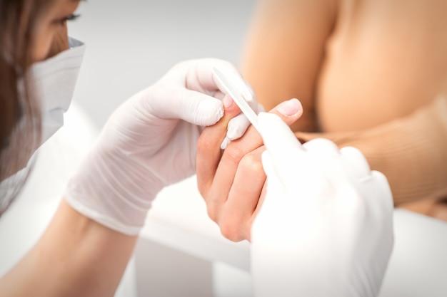 Foto de uma manicure lixa as unhas femininas com a lima em um salão de beleza