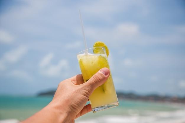 Foto de uma mão masculina segurando uma bebida com o oceano ao fundo. conceito de férias