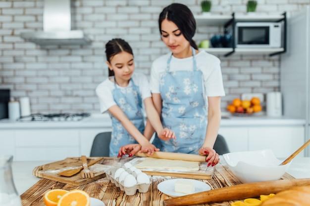Foto de uma massa e ingredientes na mesa da cozinha e duas meninas cozinhando