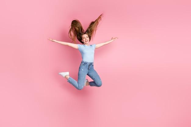 Foto de uma menina com as mãos abertas pulando isoladas em um fundo de cor rosa pastel