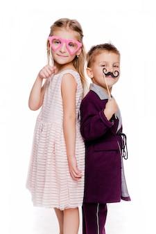 Foto de uma menina com óculos de papelão em forma de coração e um menino com bigode de papelão posando