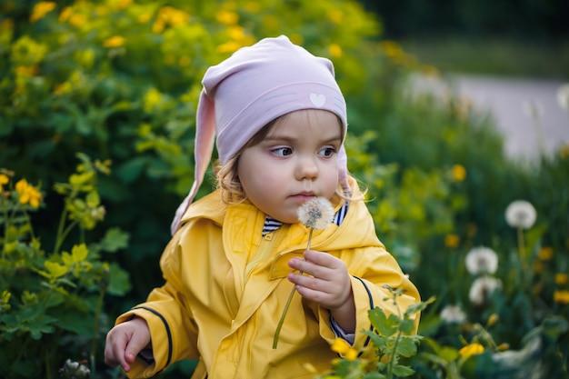 Foto de uma menina criança feliz vestindo uma jaqueta amarela e um chapéu branco, brincando em um prado, flores cercadas por uma criança e grama, brincando no campo durante o pôr do sol. conceito de infância.