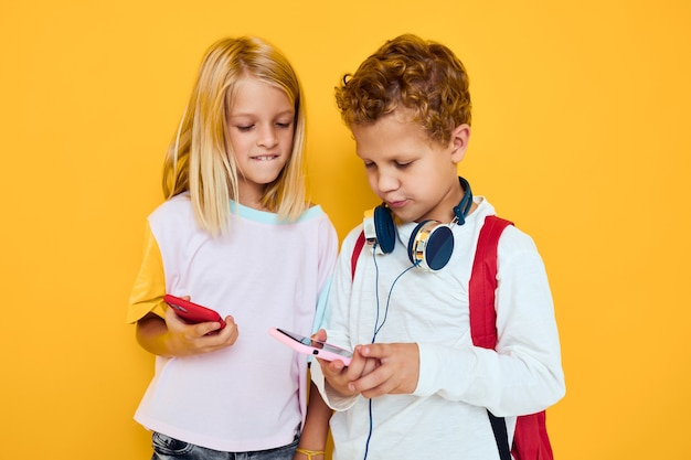 Foto de uma menina de dois filhos pequenos olhando para o fundo amarelo de comunicação de entretenimento de telefone. foto de alta qualidade
