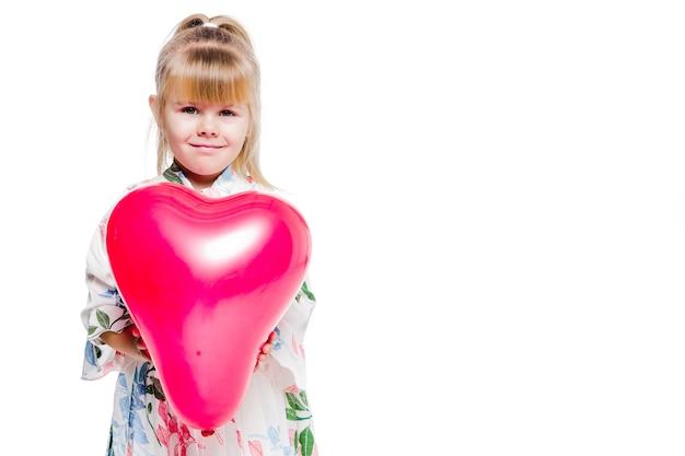 Foto de uma menina em um vestido com estampa floral segurando um balão vermelho em forma de coração