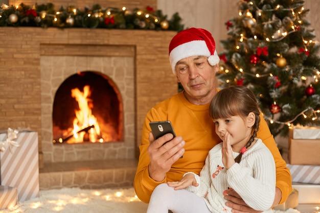 Foto de uma menina feliz e seus avós sentados no chão em um tapete macio durante a manhã de natal e conversando com a família em videochamada via celular, neta acenando com a mão para a câmera.