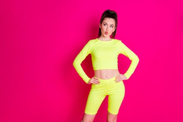 Foto de uma menina linda e fofa do esporte vestida com roupa amarela, mãos, braços, cintura, lábios, beicinho, olhar, espaço vazio, isolado, cor rosa, fundo