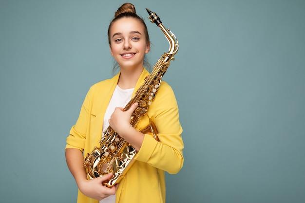 Foto de uma menina morena atraente e sorridente, usando uma jaqueta amarela na moda, isolada sobre uma parede de fundo azul segurando um saxofone, olhando para a câmera