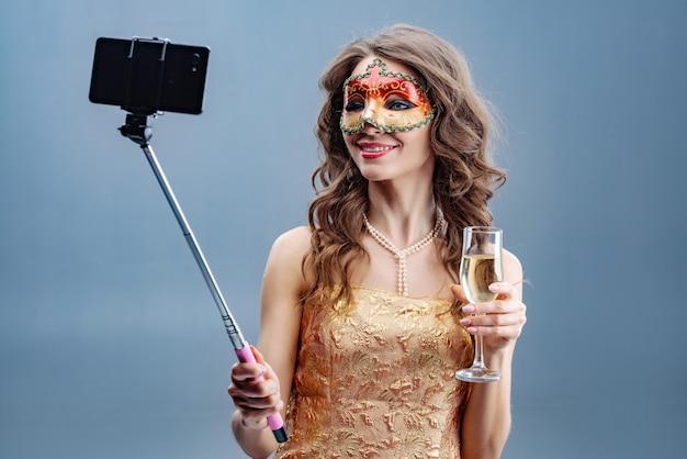 Foto de uma menina morena sorridente em uma máscara de carnaval e vestido dourado com um copo levantado faz um selfie em um telefone móvel