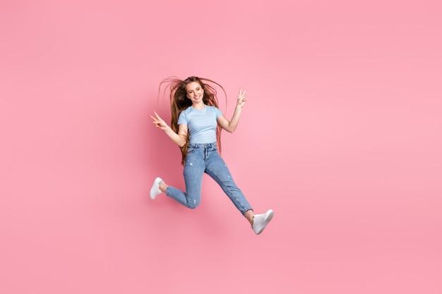 Foto de uma menina mostrando dois sinais-v pulando isolados em um fundo colorido de rosa pastel