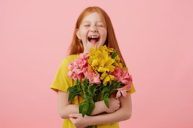 Foto de uma menina ruiva de sardas rindo petite com duas caudas, com os olhos fechados, amplamente sorrindo e parece fofa, segura o buquê, usa uma camiseta amarela, fica sobre um fundo rosa.