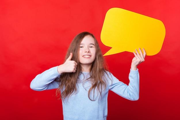 Foto de uma menina segurando um balão de fala vazio e mostrando o polegar