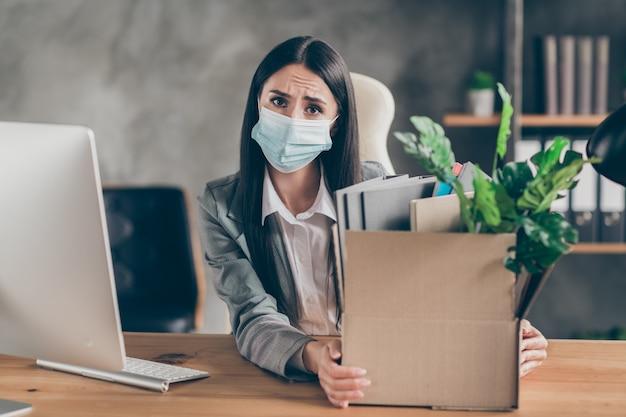 Foto de uma menina triste e frustrada, agente de marketing, representante, sente-se, mesa, trabalho perdido corona vírus quarentena empresa crise usar máscara médica na estação de trabalho