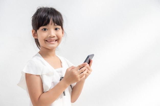 Foto de uma menina usando um telefone celular isolada sobre um fundo branco