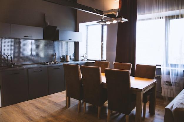 Foto de uma mesa de madeira com cadeiras de madeira perto das cortinas da janela em uma cozinha com interior preto