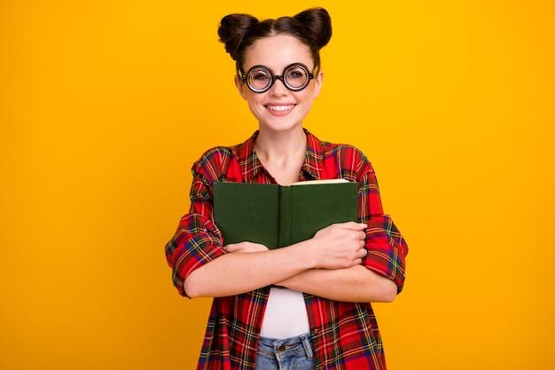 Foto de uma moça bonita segurando o livro perto do peito.