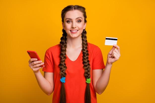 Foto de uma moça bonita segurando um cartão de crédito de telefone na parede amarela