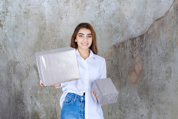 Foto de uma modelo de garota bonita com cabelo comprido segurando caixas de presentes