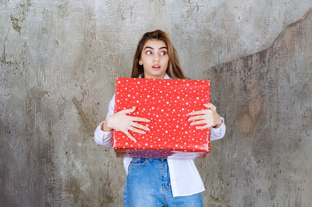 Foto de uma modelo de garota bonita com cabelo comprido segurando um grande presente vermelho