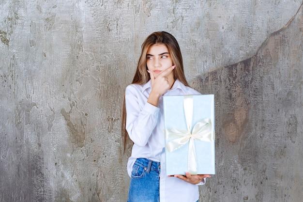 Foto de uma modelo pensativa com cabelo comprido segurando um grande presente