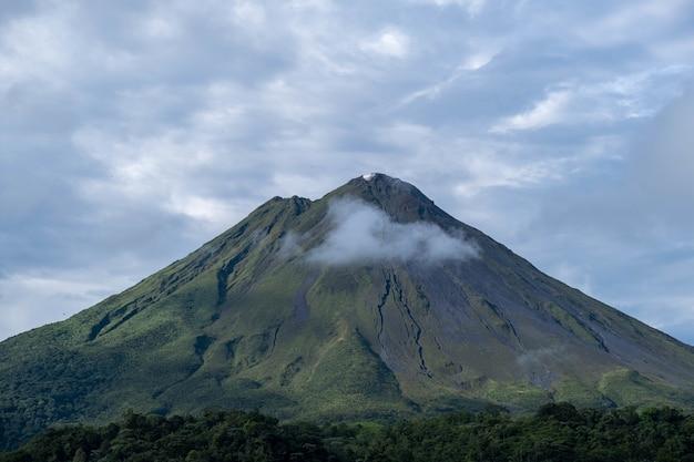 Foto de uma montanha gigante de tirar o fôlego coberta por florestas, brilhando sob o céu nublado
