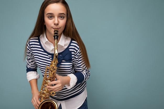 Foto de uma morena muito positiva, feliz, feminina, adolescente, vestindo uma manga comprida listrada elegante em pé, isolada sobre a parede de fundo azul, tocando saxofone, olhando para a câmera