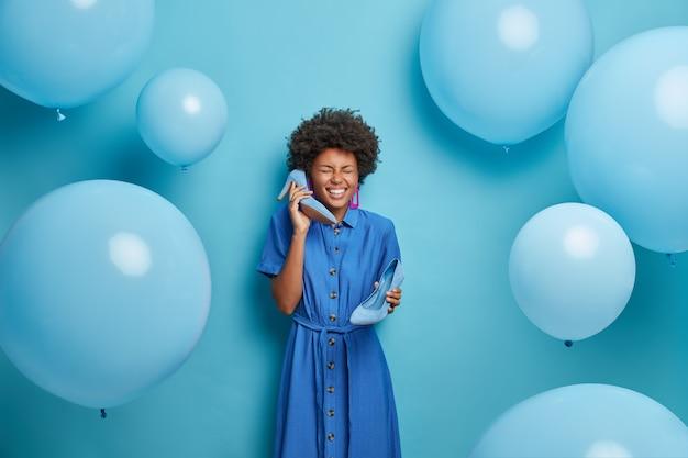 Foto de uma mulher afro-americana alegre e exagerada ri e se diverte antes de se vestir para uma festa discoteca, imita conversa telefônica, segura sapatos de salto alto perto das orelhas, isolada na parede azul