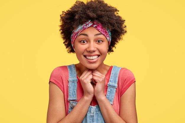 Foto de uma mulher afro-americana alegre mantém as mãos juntas perto do queixo e sorri amplamente