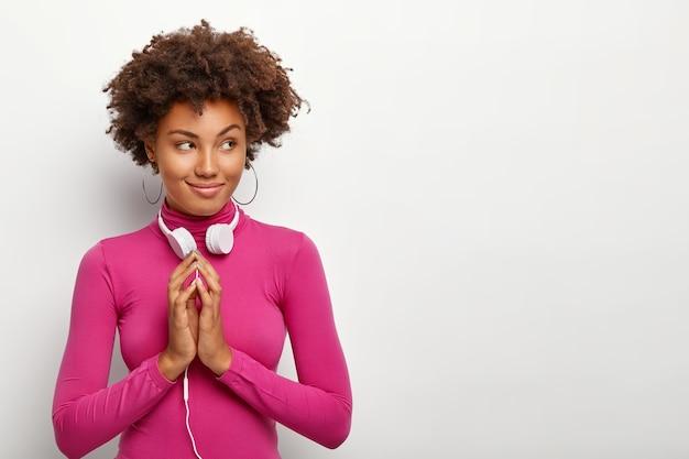 Foto de uma mulher afro-americana atenciosa com as palmas das mãos unidas, usando uma blusa de gola alta rosa, olhando de lado, isolada na parede branca