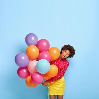Foto de uma mulher afro-americana chocada com expressão de omg, segurando muitos balões de ar de hélio coloridos, vestida com uma camisa e saia vivas
