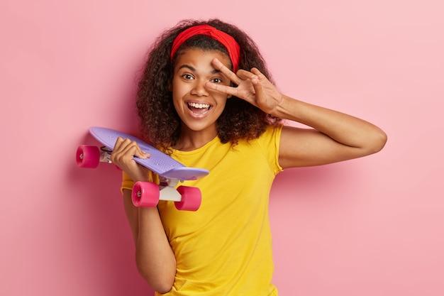 Foto de uma mulher afro-americana de aparência agradável e nítida faz um gesto de paz, sorri positivamente, usa uma faixa vermelha na cabeça e uma camiseta amarela, segura o skate isolado sobre a parede rosa. conceito de lazer