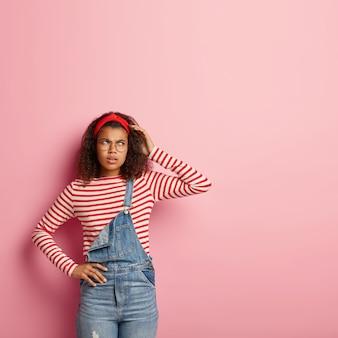 Foto de uma mulher afro-americana zangada e pensativa com expressão pensativa, coça a cabeça, usa bandana vermelha, suéter listrado e macacão jeans