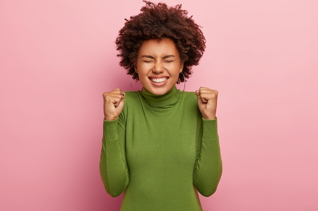 Foto de uma mulher afro radiante com os punhos cerrados em triunfo, sorri amplamente e regozija-se com a nova conquista