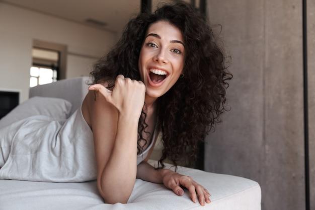 Foto de uma mulher alegre e animada com cabelo longo cacheado, vestindo roupas de lazer de seda, olhando para o lado e apontando o dedo para copyspace, enquanto estava deitada no sofá em casa