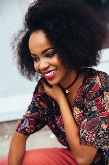 Foto de uma mulher americana afro atraente sorridente com maquiagem colorida e dentes brancos