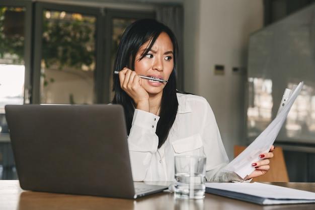 Foto de uma mulher asiática confusa e intrigada de 20 anos vestindo roupas de escritório, segurando e lendo documentos em papel com perplexidade, enquanto trabalhava em um laptop