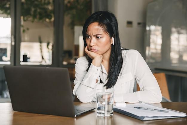 Foto de uma mulher asiática perplexa de 20 anos, vestindo uma camisa branca e fones de ouvido bluetooth, franzindo a testa e olhando para o laptop com perplexidade, enquanto está sentada à mesa no escritório