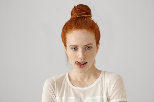 Foto de uma mulher atraente e tentadora com cabelo ruivo preso, lambendo os lábios