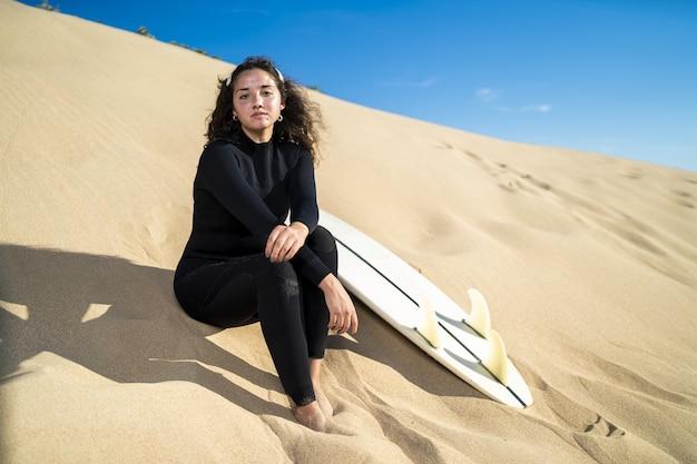 Foto de uma mulher atraente sentada em uma colina arenosa com uma prancha de surfe ao lado