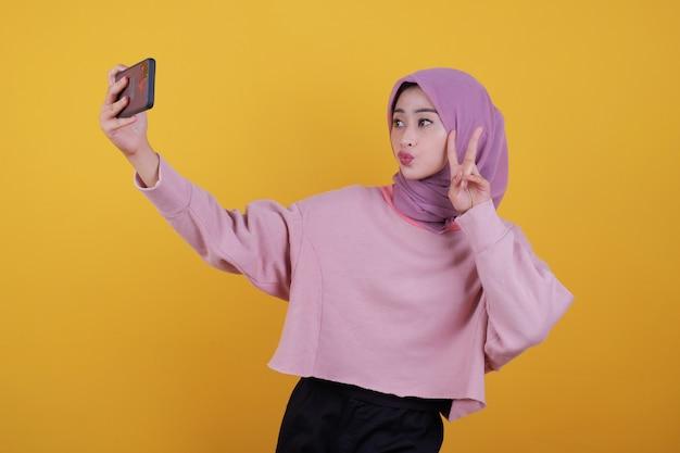 Foto de uma mulher bonita e atraente mantém um celular moderno na mão, anuncia o novo gadget de seu favorito, tire uma foto