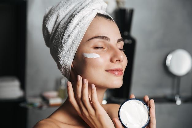 Foto de uma mulher bonita enrolada em uma toalha aplicando creme no rosto
